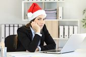 Sad Office Worker Working In Christmas Time Looking At Camera poster