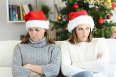 Angry Roommates Or Sisters In Christmas Sitting On A Couch In The Living Room At Home poster