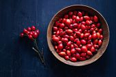 Freshly picked rose hips. Wooden bowl of rose hip or rosehip, commonly known as the dog rose (Rosa c poster