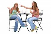 Two beautiful young woman having lunch together at small bistro table.  Laughing and pointing to the left.
