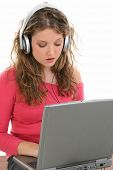 Beautiful Teen Girl with Headphones and Laptop.  Listening and singing to music. Shot in studio over white.