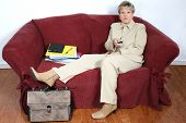 Woman in beige suit with remote, sitting on couch with stack of work papers beside her.