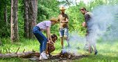 Company Friends Or Family Making Bonfire In Forest Nature Background. Friends Working As Team To Kee poster