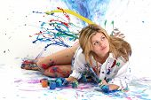 Beautiful young woman laying in paint covered studio.  Paint splattered on walls, floor, model.  Sho