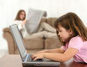 Niña cinco años poner en la mesa con el ordenador portátil mientras mamá (fuera de foco) lee el periódico en sofá. SH