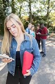 Unhappy Teenage Girl Being Bullied By Text Message At School poster