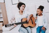 Little Girl With Mother Sing And Play Guitar. Happiness Time With Beautiful Mother. Painter And Peop poster