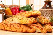 Bundle of hot garlic bread sticks in kitchen or restaurant.