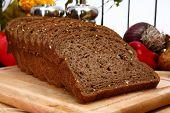 Loaf of dark wheat bread in kitchen.