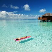Woman swim and relax on inflatable mattress in the sea. Happy island lifestyle. White sand, crystal- poster