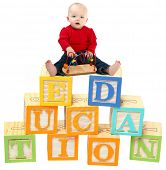 14 month old baby girl sitting on colorful toy blocks that read EDUCATION.