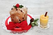 Panettone Christmas cake and glass of eggnog with winter flora of holly, fir and mistletoe on rustic poster