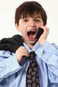 Adorable seven year old french american boy in over sized suit over white background yelling in cell
