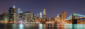 image of brooklyn bridge  - New York City Manhattan skyline panorama with Brooklyn Bridge and office skyscrapers building in at dusk illuminated with lights at night - JPG