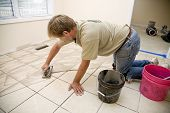stock photo of grout  - Installer filling ceramic tile with grout home is being updating for resale on housing market - JPG
