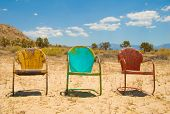 Three Vibrant, Vintage Charis Sitting Empty In The Hot Desert
