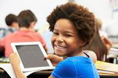stock photo of pupils  - Pupil In Class Using Digital Tablet - JPG