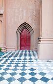 Puerta de la iglesia roja más allá del Patio de damero