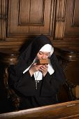 Young nun kissing an old prayer book after praying (shot in a 17th century church interior)