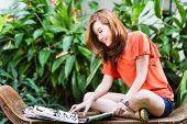 Young Chinese girl sitting on a bench in a tropical environment and reading a fashion magazine, she