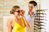Young woman at optician with glasses, they are looking for sunglasses