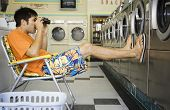 picture of laundromat  - Man with lawn chair and binoculars at laundromat - JPG