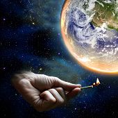 stock photo of day judgement  - Hand holding a match and the planet earth warming up - JPG