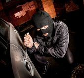 pic of scum  - Robber and the car thief in a mask opens the door of the car and hijacks the car - JPG