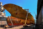 foto of sandblasting  - Workers sandblasting a large cargo ship from rust and corrosion - JPG