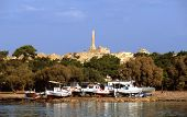 pic of argo  - The last standing column of the Temple of Apollo in ancient Aegina rises like an admonishing finger above a makeshift boat repair yard on the shores of the Aegean Sea - JPG