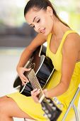 beautiful woman playing guitar at home
