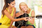 stock photo of tutor  - smiling beautiful music teacher tutoring young girl to play guitar - JPG
