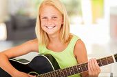 happy pre teen girl practicing  guitar at home