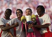 Soccer team triumphantly holding trophy