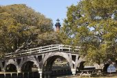foto of whalehead club  - The Currituck Beach Lighthouse rises behind the famous Footbridge in Corolla - JPG