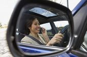 View of woman on her cell phone through the rear view mirror of car