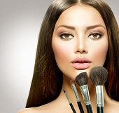 Beauty Girl with Makeup Brushes. Natural Make-up for Brunette Woman with Brown Eyes. Beautiful Face.