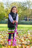 Attractive preschool autumn girl with a kid umbrella