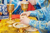 Christian sacrament. Hands of priest refracting bread during orthodox liturgy ceremony