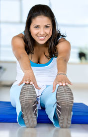 stock photo of workout-women  - woman doing stretching exercises on the floor at the gym - JPG
