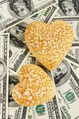 Love and money concept. Heart-shaped stones and American currency close up.