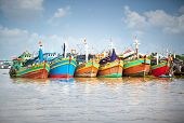A row of colorful fishing boats berthed at the port in the Mekong Delta, Vietnam
