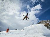 foto of snowboarding  - Jumping snowboarder in mountains on the snowboard on blue sky background - JPG