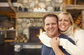 stock photo of appalachian  - Happy Affectionate Couple at Rustic Fireplace in Log Cabin - JPG