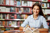 picture of clever  - Portrait of pretty student looking at camera while working in college library - JPG