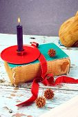Lit candle in a red candle holder with old book in red ribbon on antique table.