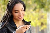 picture of arabic woman  - Portrait of a beautiful woman typing on the smart phone in a park with a green unfocused background - JPG