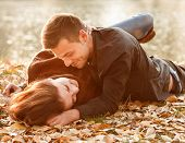 picture of heterosexual couple  - young couple lying down near lake smiling having good time - JPG
