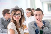 Two posing highschool students smiling in classroom