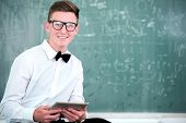 Modern looking student with bowtie in front of blackboard